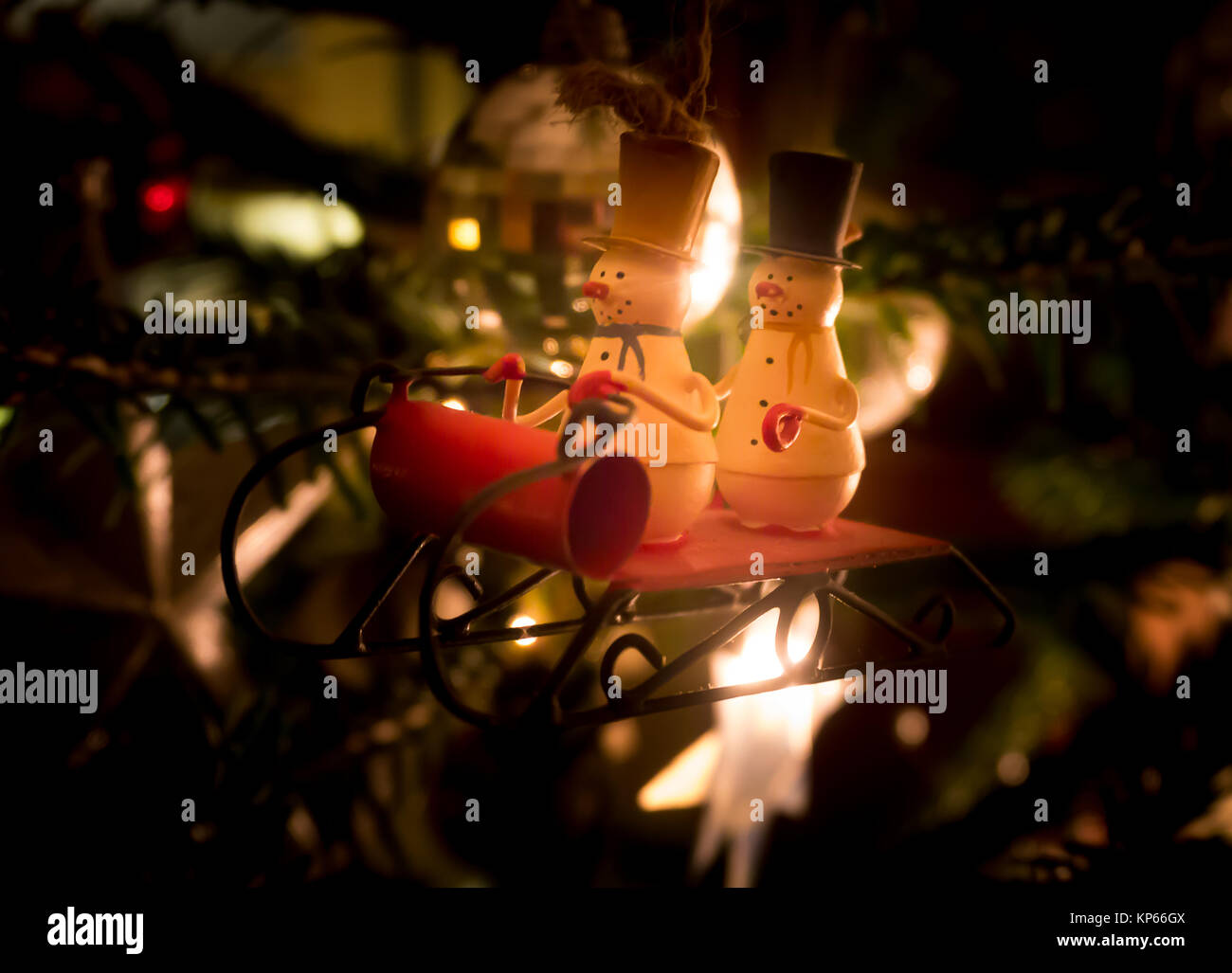 Traditional Christmas tree decoration, two snowmen in top hats on a sledge - Stock Image