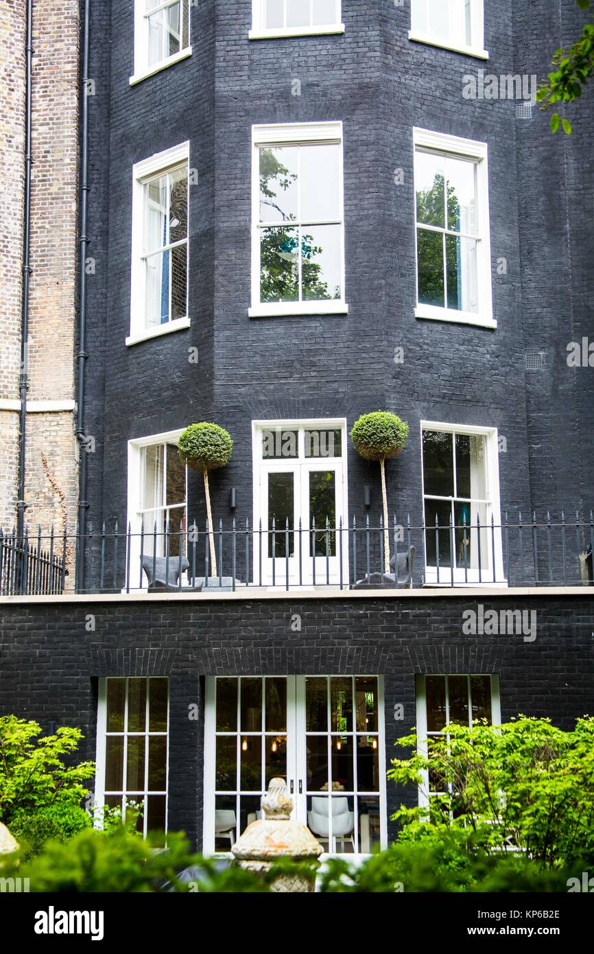 Very tall and modern dark grey town house with many windows and adorned with french doors and many greens in the garden
