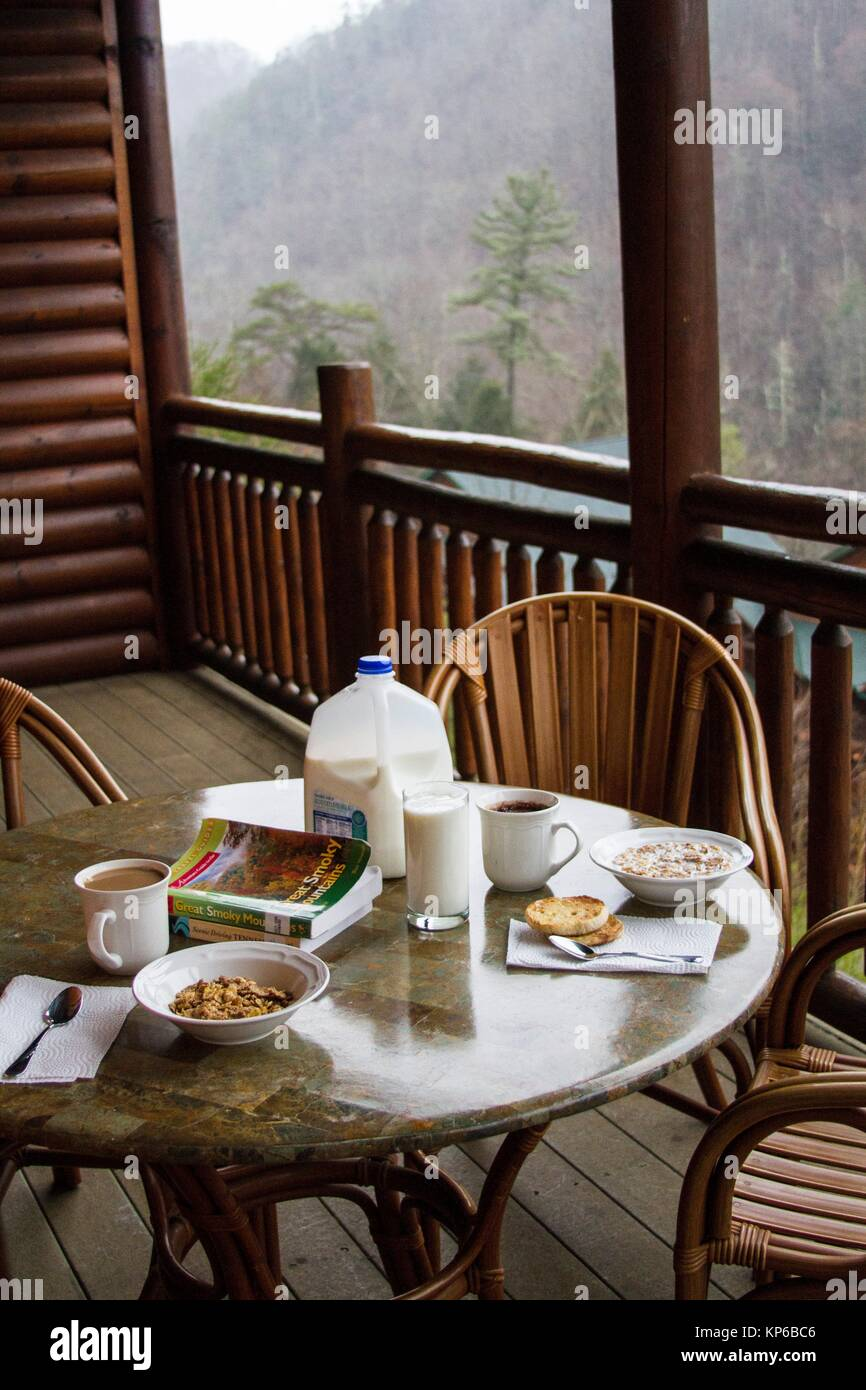 Breakfast table set with milk and cereals on the wooded balcony of a ski resort. The view from the mountains is - Stock Image