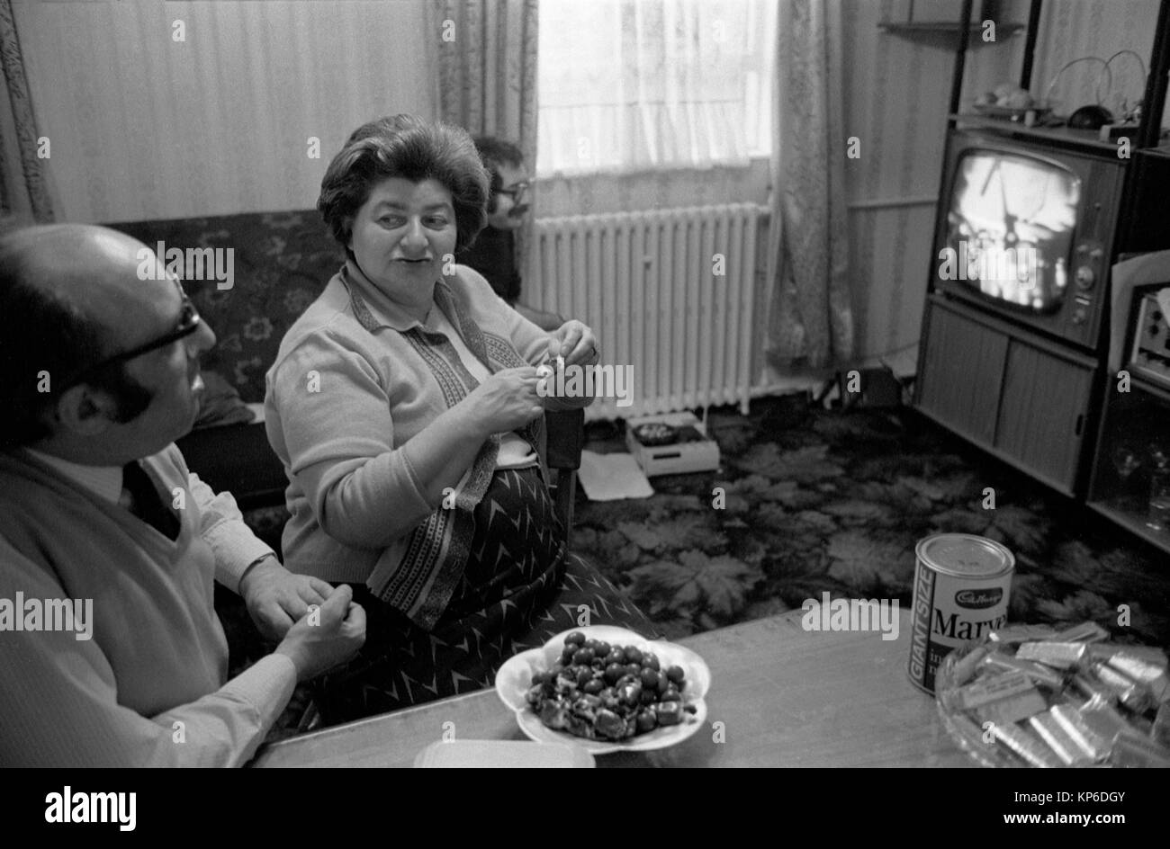 1970s family at home Uk, watching television London. 70s England Marvel was a very popular powdered milk, spoon - Stock Image