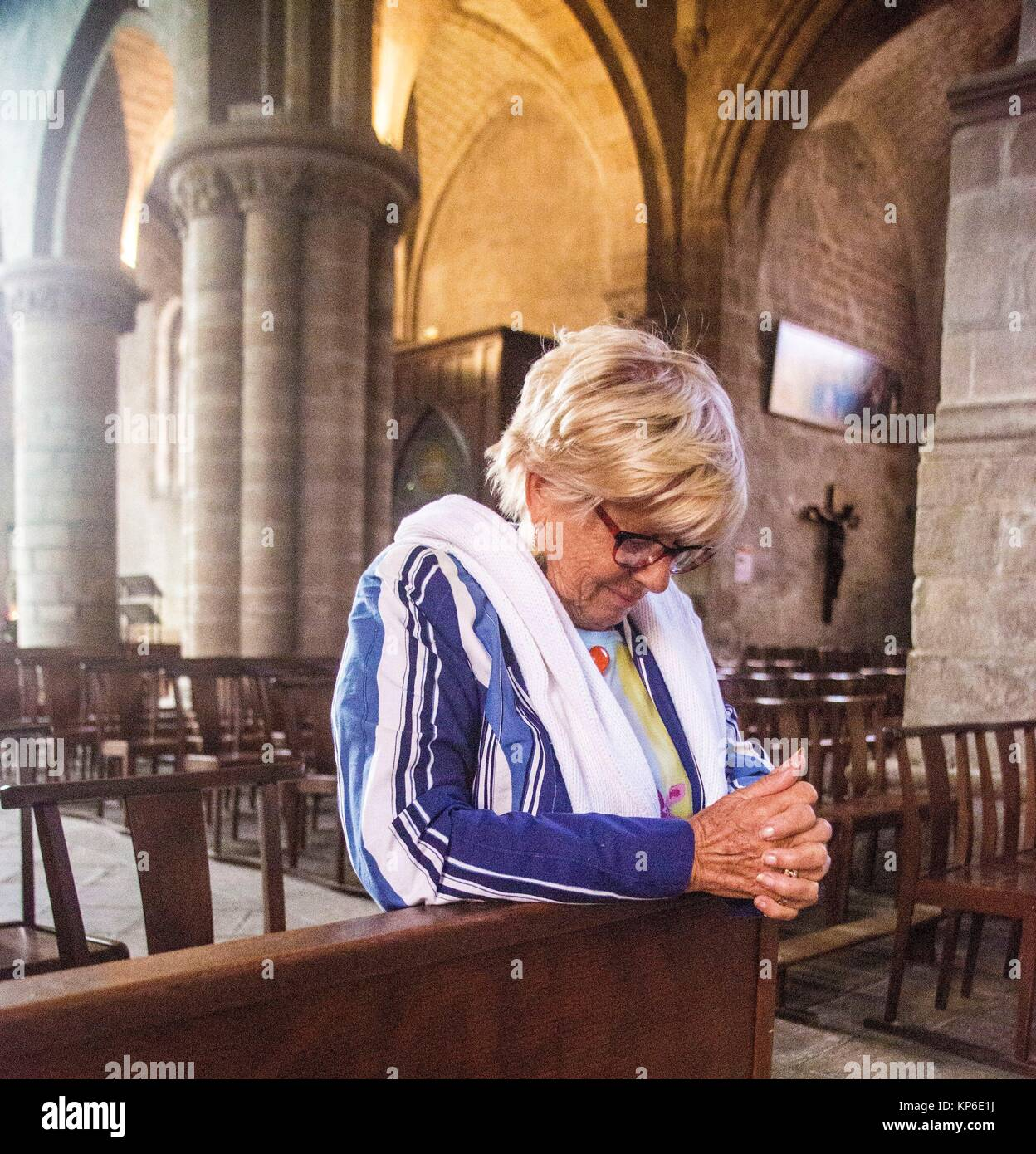 Older mature senior blond hair woman sitting at the pew and being very spiritual as she prays to god in a church - Stock Image