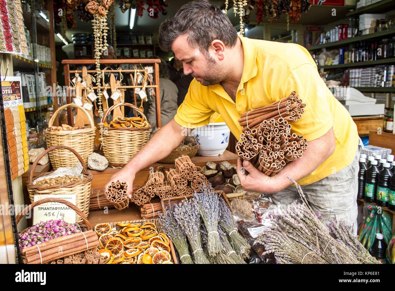 Caucasian man organizing Dry oranges slices, and cinnamon sticks tied together for sale in the street in bulk. They - Stock Image