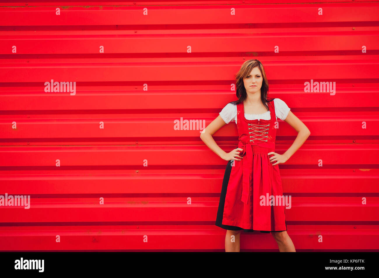 Frau im roten Dirndl vor roter Wand - Lady in red - Stock Image