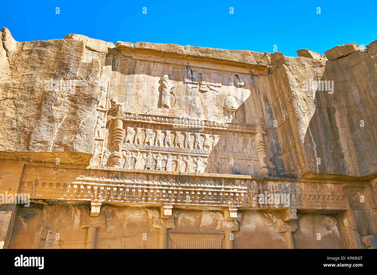 The ancient carvings on the facade of cut in rock Tomb of Artaxerxes III, Persepolis, Iran. - Stock Image