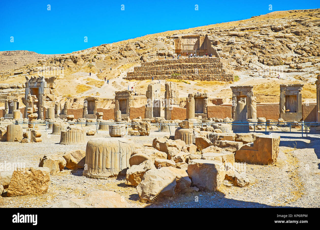 Discover Persepolis archaeological site with its ancient landmarks - tomb on the mountain slope and Hundred Columns - Stock Image