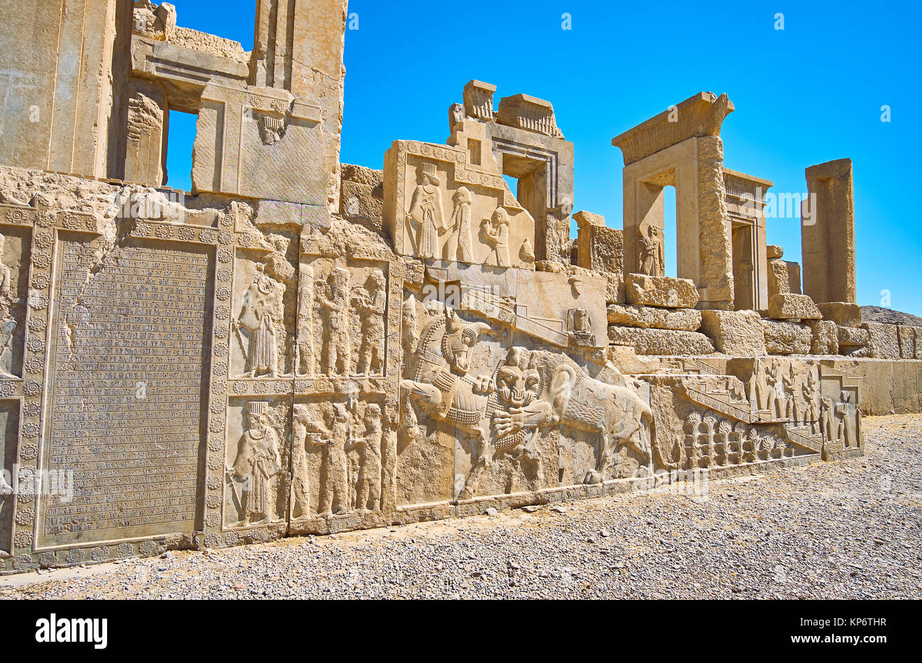 The facade of ruined Tachara palace with ancient Persian text and carvings of soldiers, courtiers, lion biting the - Stock Image