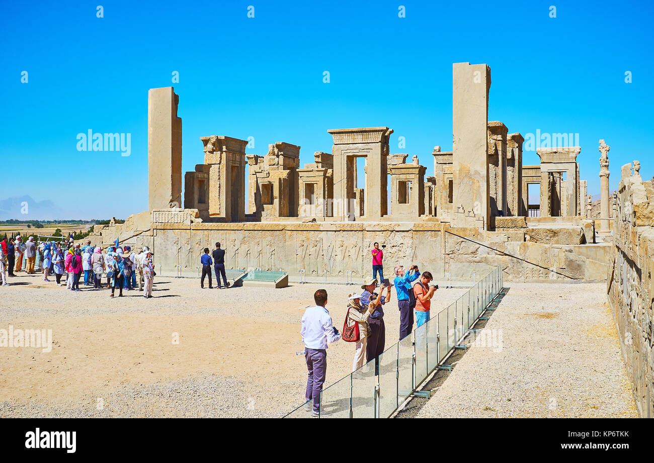 PERSEPOLIS, IRAN - OCTOBER 13, 2017: Numerous tourist groups at the Tachara palace wall with preserved reliefs, - Stock Image