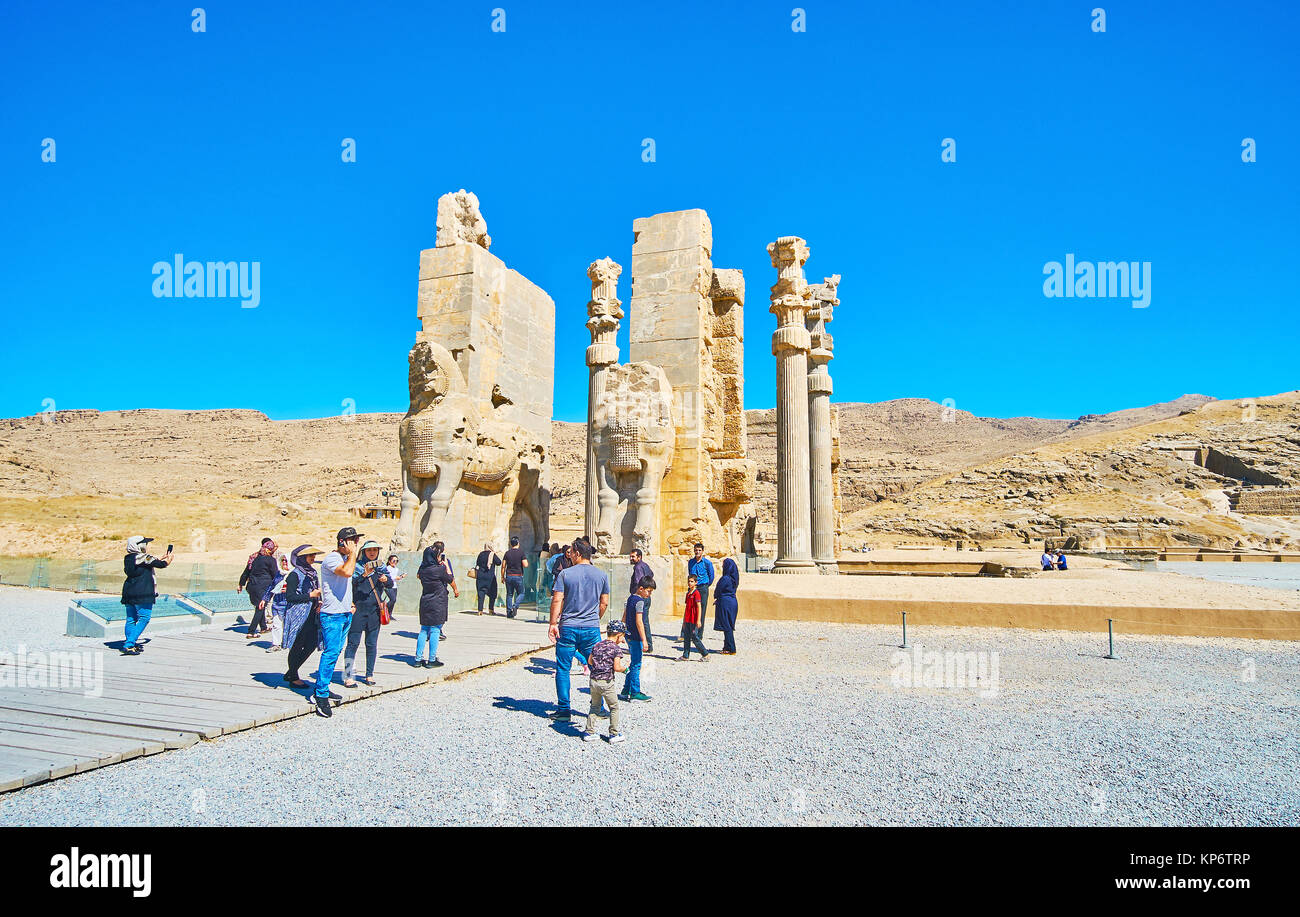 PERSEPOLIS, IRAN - OCTOBER 13, 2017: The tourists enjoy the ruins of All Nations (Xerxes) Gate of Persepolis with Stock Photo