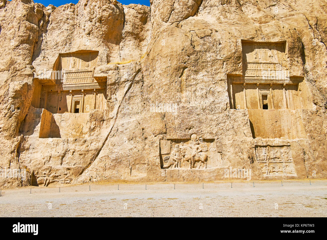 The giant tombs of Naqsh-e Rustam archaeological site are neighboring with equestrian reliefs, carved in rocky cliff, - Stock Image