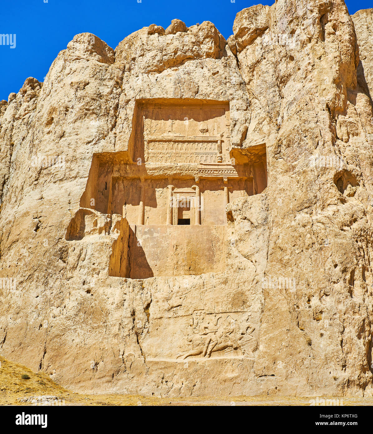 The carved in rock Mausoleum of Darius II in Naqsh-e Rustam Necropolis, from below can be seen preserved equestrian - Stock Image