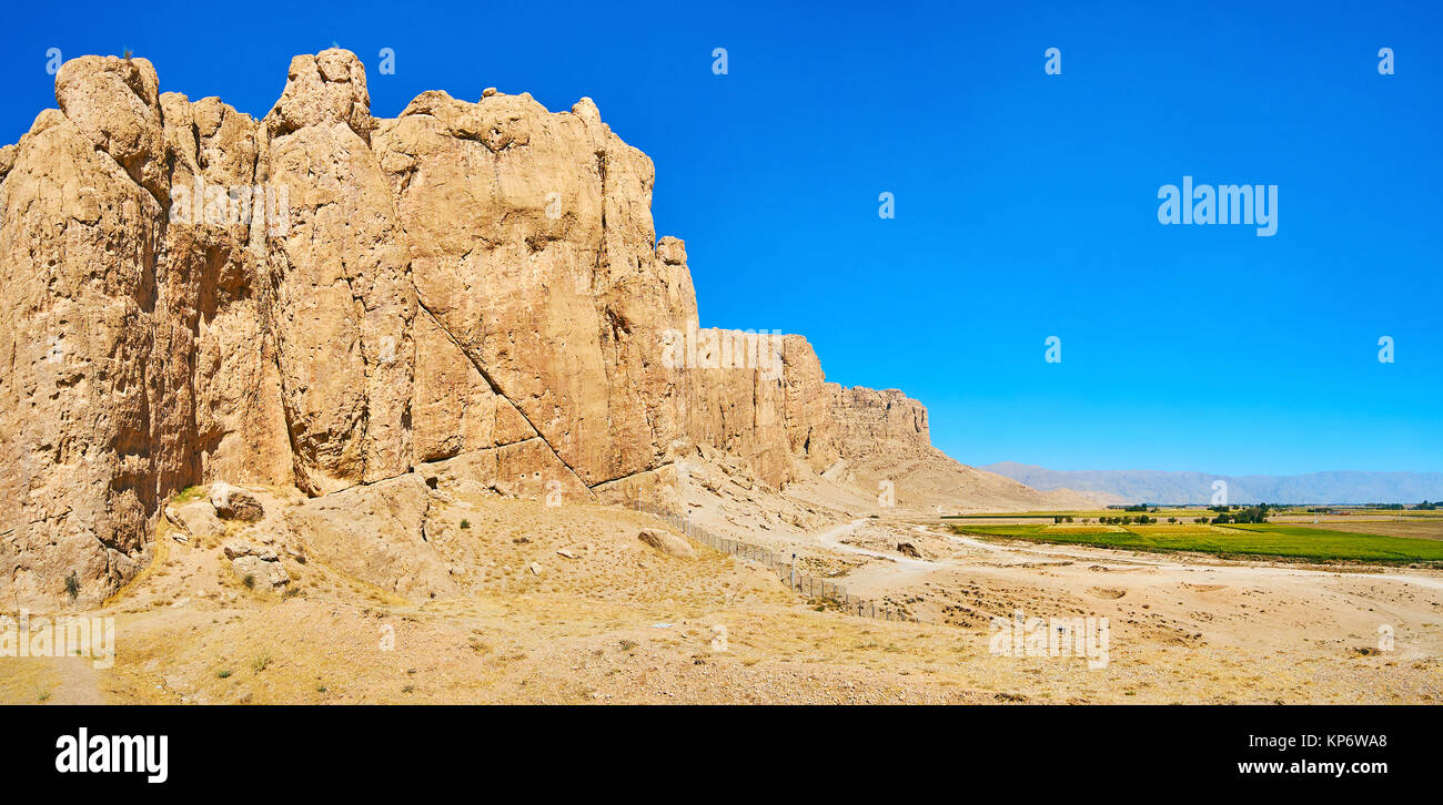 Panorama of yellow rocky cliffs and the agricultural lands, stretching along the range, Naqsh-e Rustam, Iran. - Stock Image