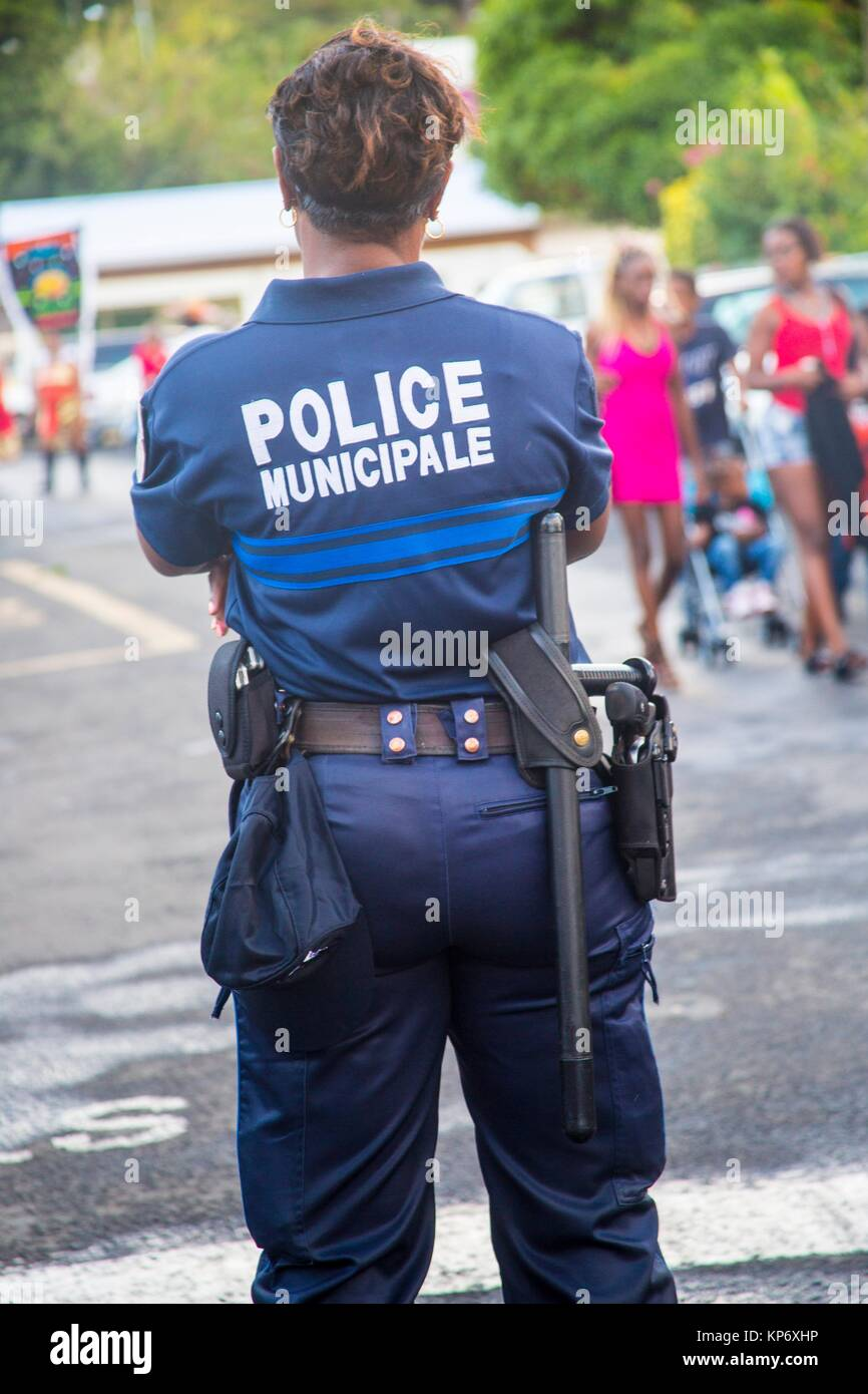 Police woman standing in the street with all her gear on, guns, and more. - Stock Image