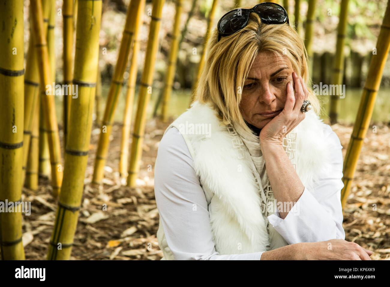 Melancholic blond woman sitting in the middle of bamboos. She is dressed in white, has sunglasses on and looks sad, - Stock Image