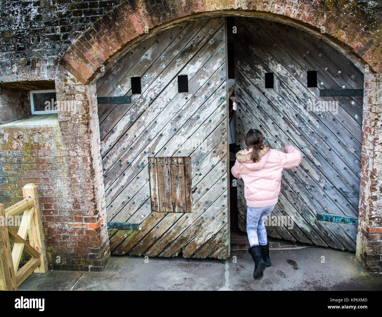 Preteen Caucasian Girl Trying To Push An Old Wood Heavy Door In An Old Fort.