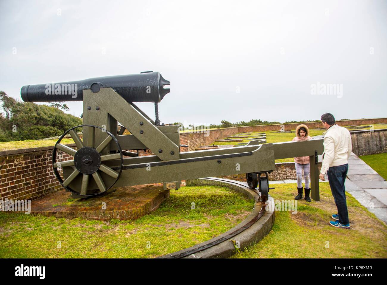 Handsome caucasian dark hair Father and preteen caucasian daughter taking a look at old canons in an old fort. Fort Stock Photo