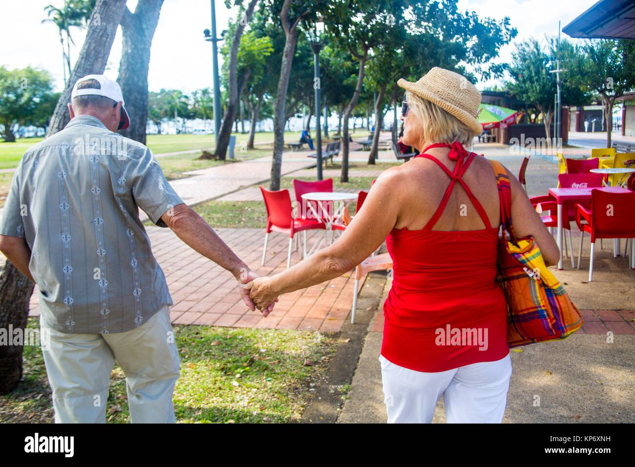 Older mature retired caucasian couple holding hands in the streets of Fort de France on a vacation. He wears a baseball - Stock Image