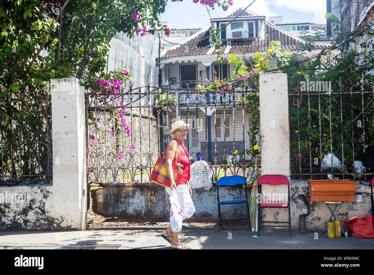 Caucasian older senior retired woman walking the streets of fort de france in Martinique in front of an iron gate. - Stock Image
