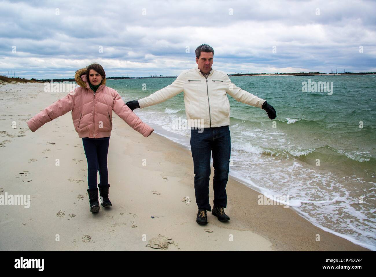 Father playing with his daughter and playing in the wind on the beach and letting themselves flow - Stock Image