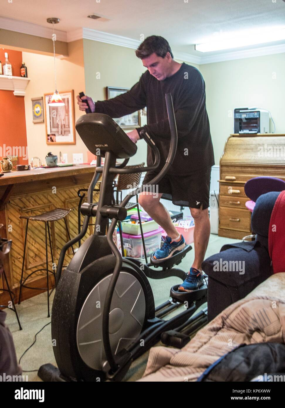 Man at home on a treadmill working out and having a hard time. - Stock Image