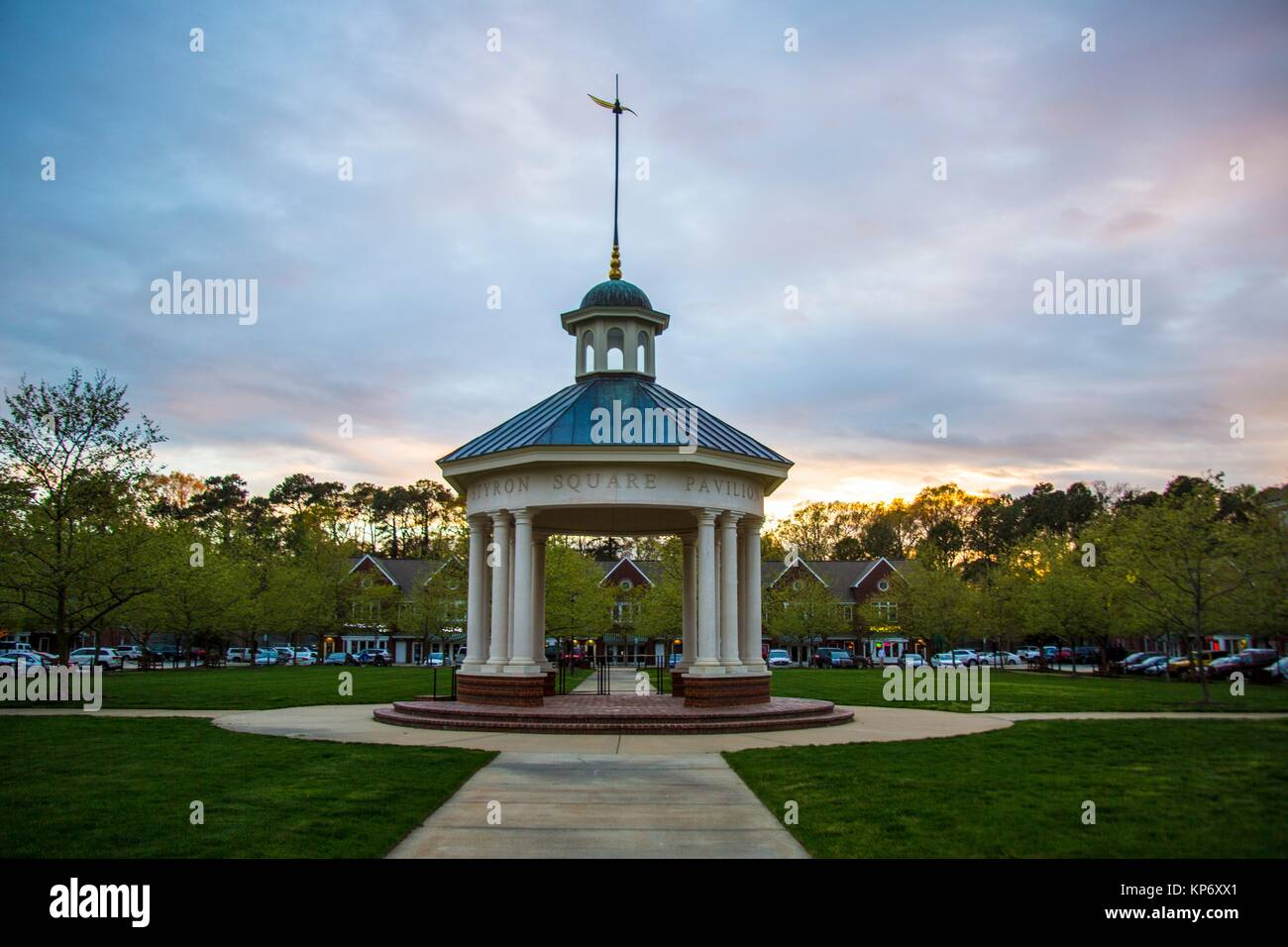 round beautiful Gazebo in a town square, in a town grass area where the sunset is setting. - Stock Image