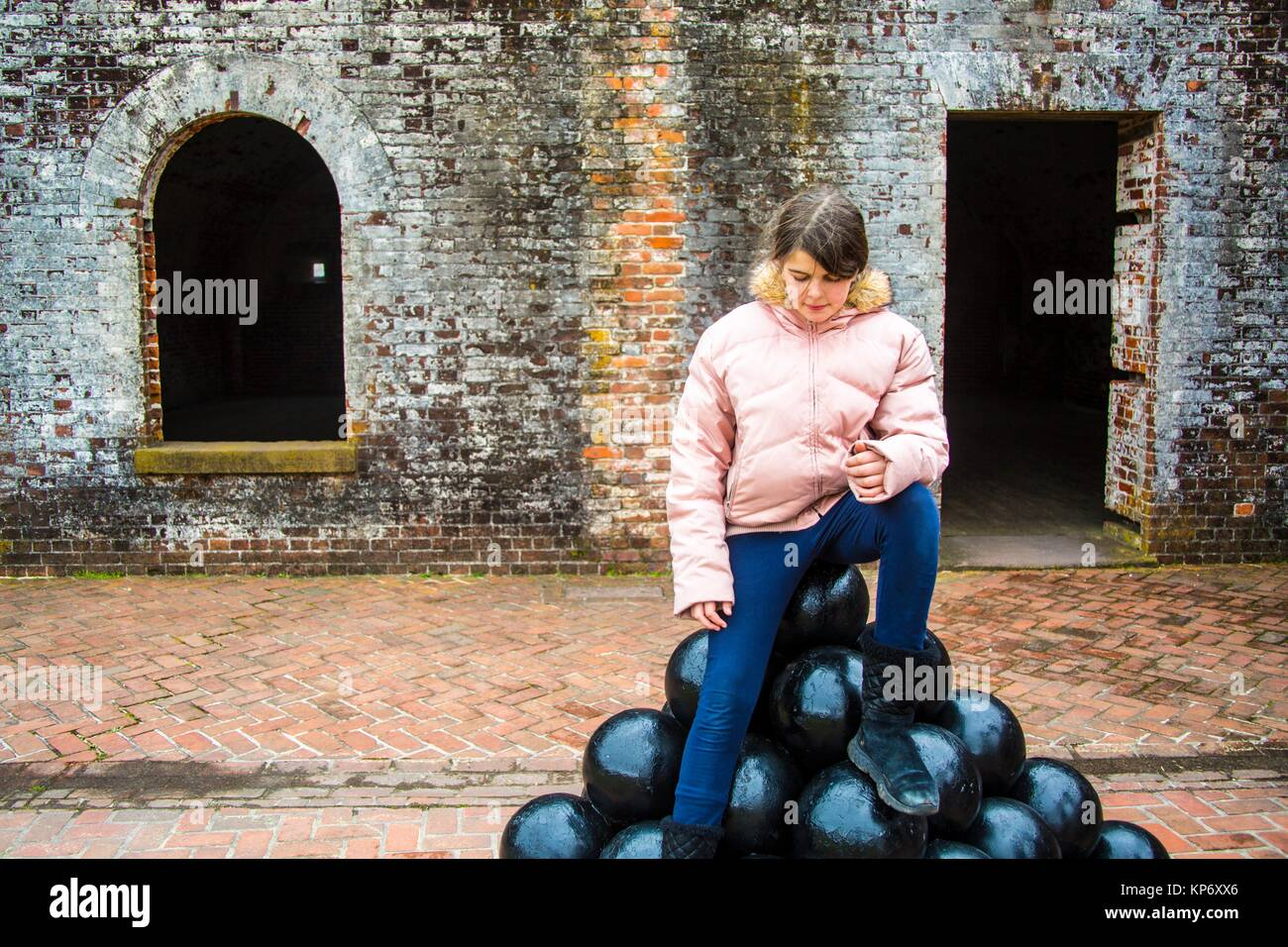 beautiful preteen caucasian girl sitting on a pyramid pile of canon balls in an old fort. She is dress warmly and - Stock Image