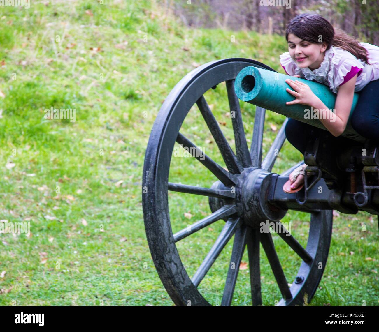 Old fashion brown wheels with green canon in the middle of an old war field with a preteen laying on it and smiling - Stock Image