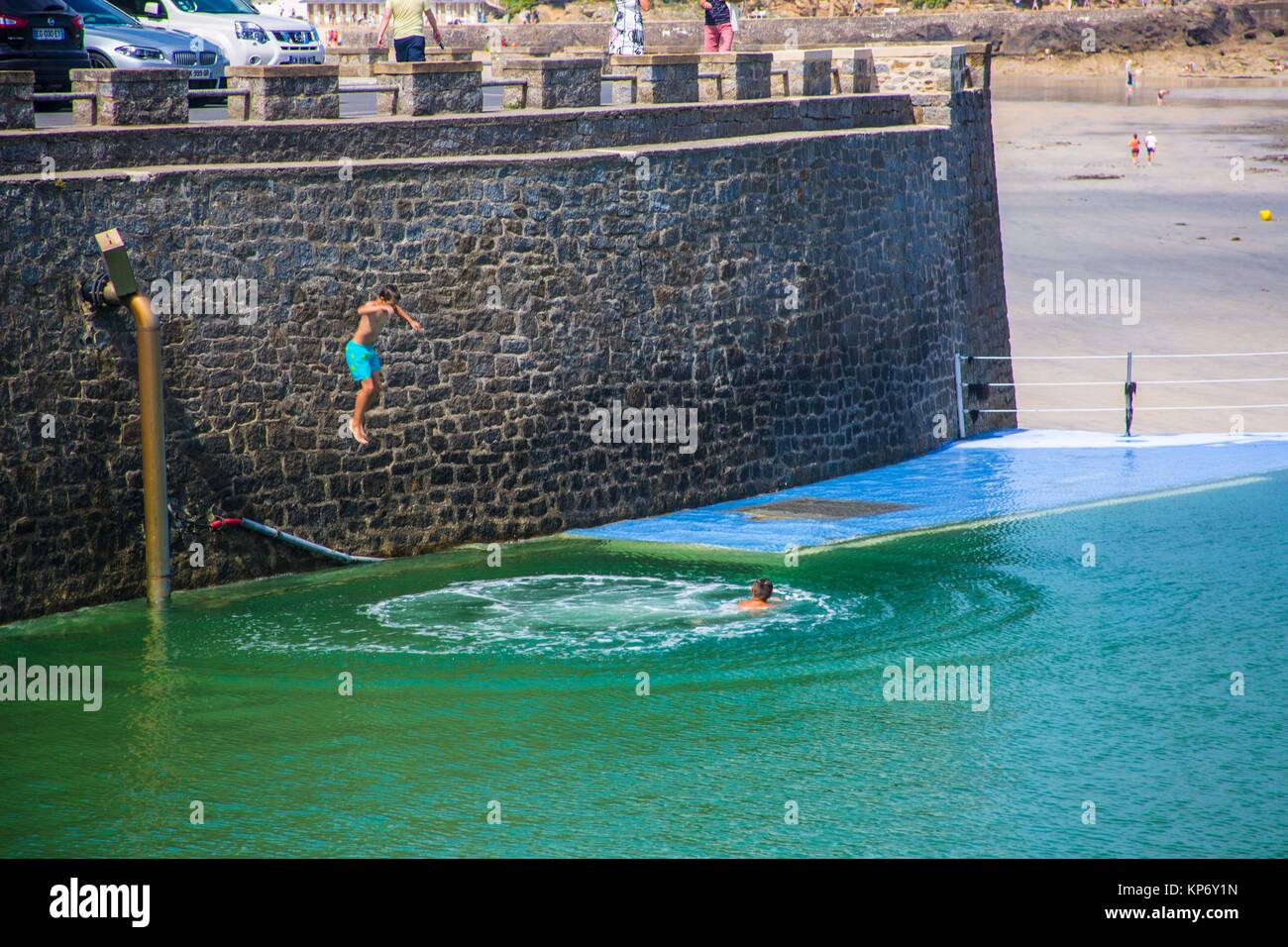 Lagoon like pool in the cote d´emeraude along the beach in Dinard, Brittany, France. We can see a teen boy - Stock Image