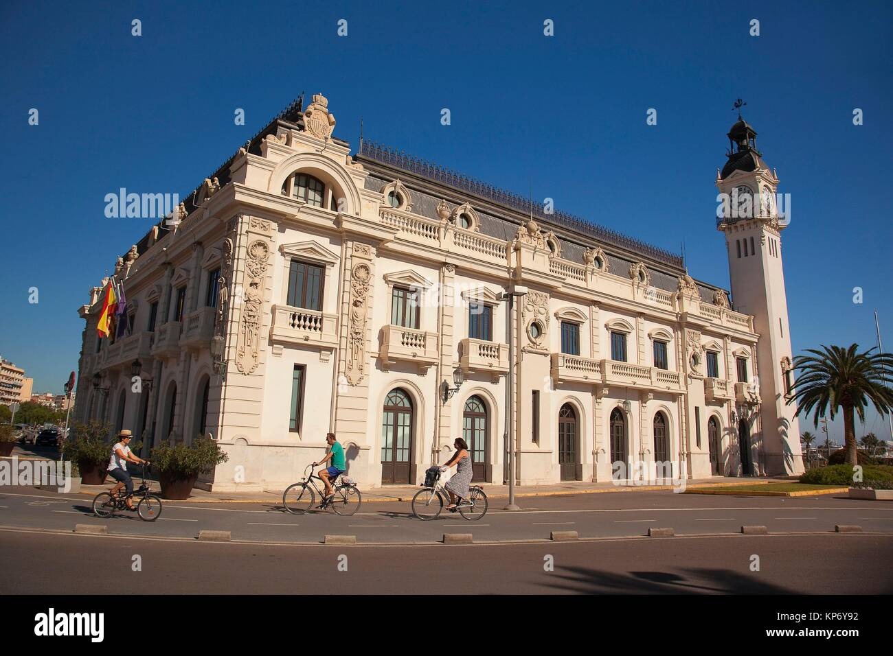 Cyclists in front of the Port Authority Building with its beautiful clock tower, Valencia, Spain, Europe - Stock Image