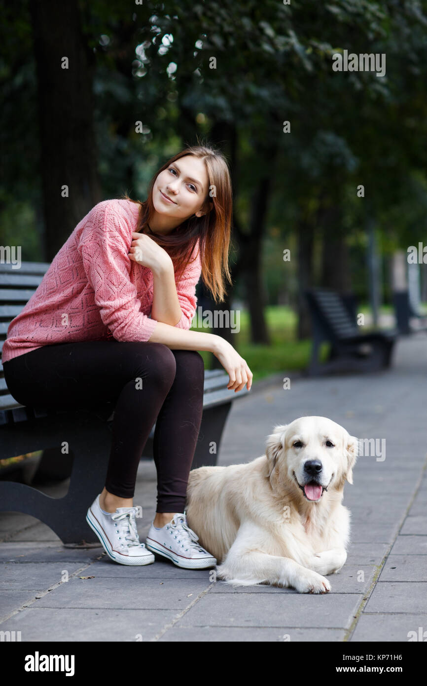 Photo of woman sitting on bench on walk with dog - Stock Image