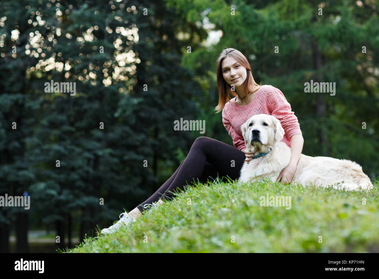 Image from below of girl sitting with dog on green lawn - Stock Image