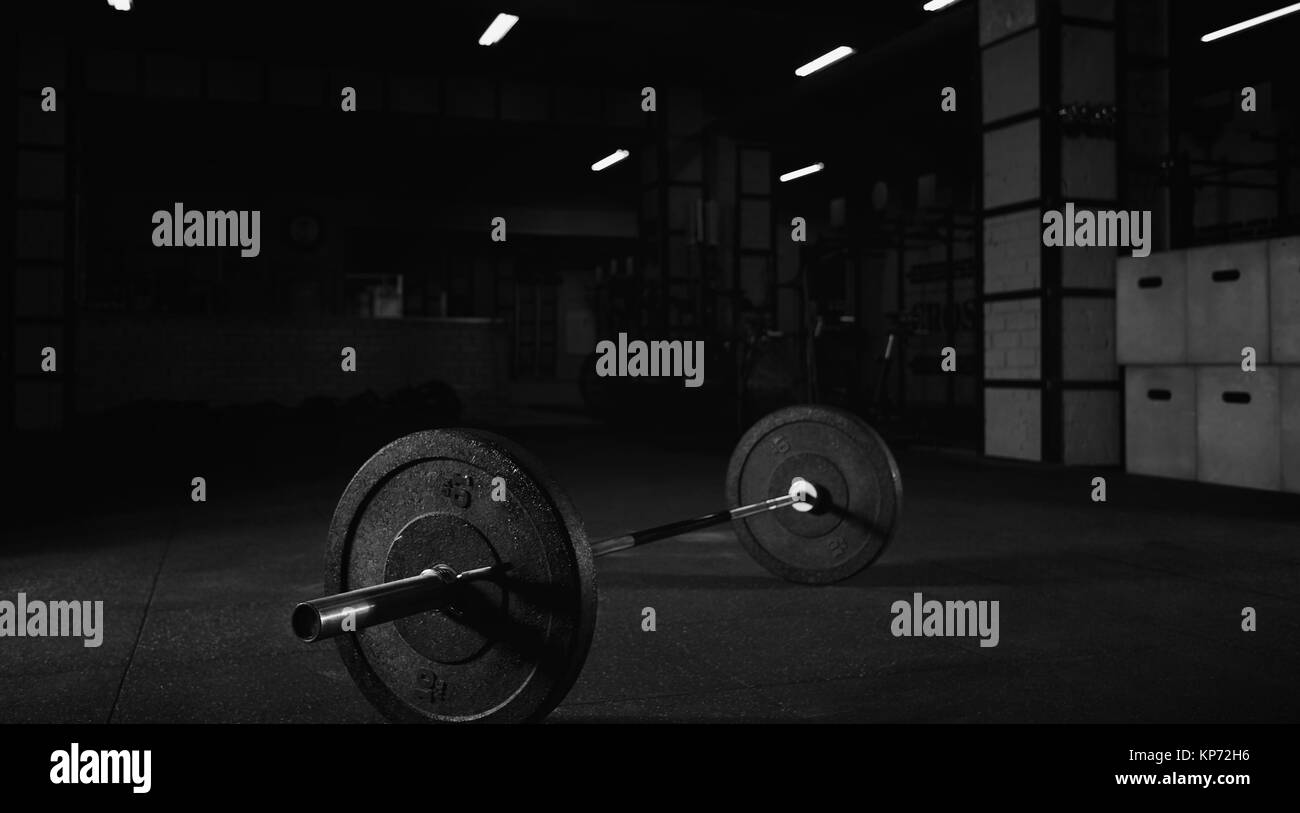 Heavy barbell on the floor of a gym studio - Stock Image