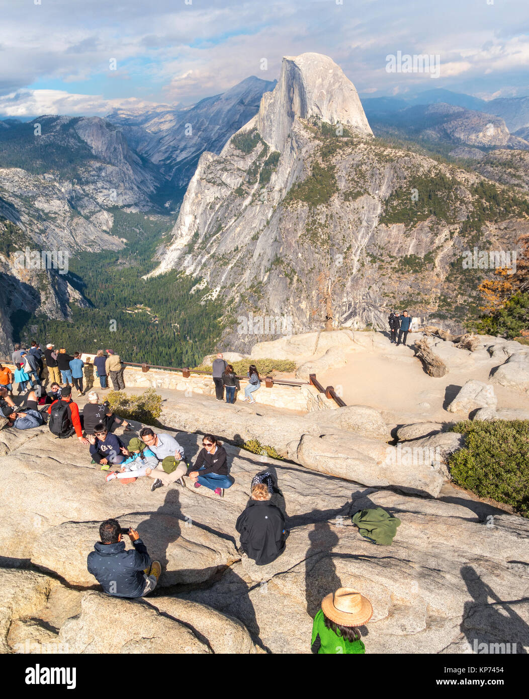 Half Dome Yosemite view from Glacier Point Overlook with people family taking pictures. Yosemite National Park California - Stock Image