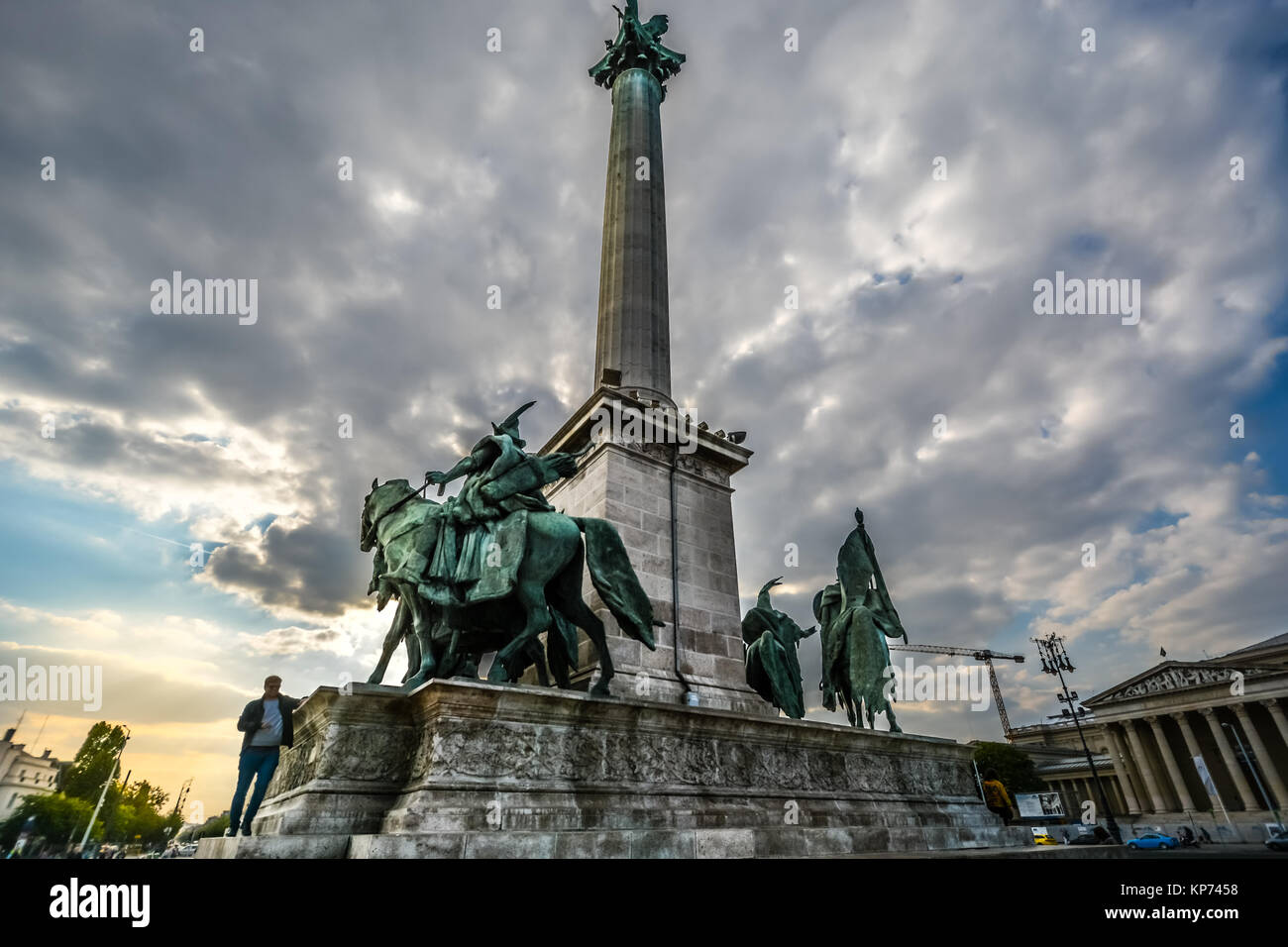 A young man walks on the Millenium monument in Heroes Square, or Hosok tere at the city park in Budapest Hungary Stock Photo