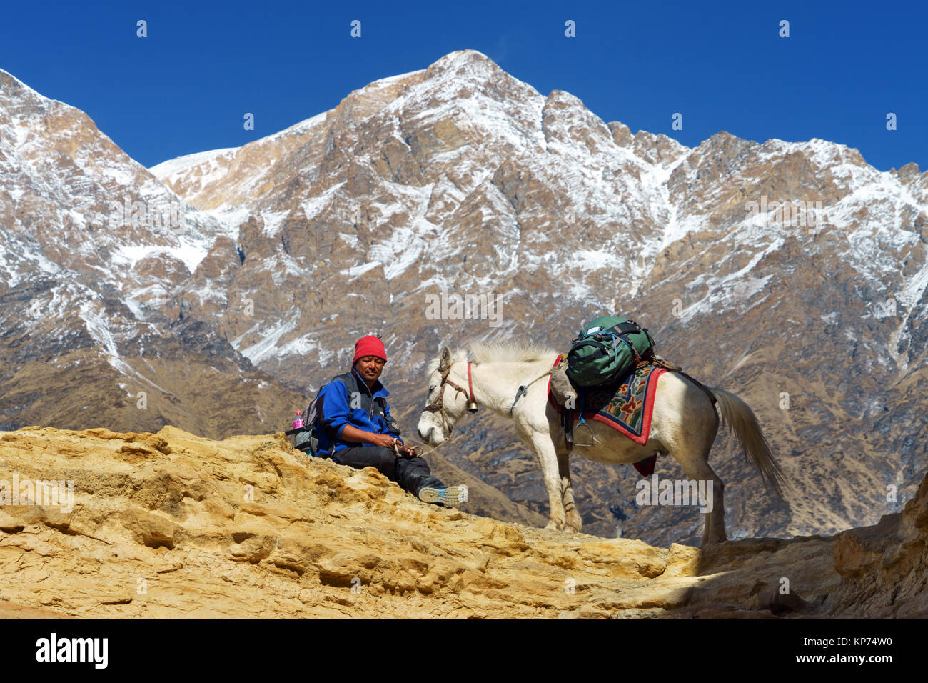 Nepalese man and his horse taking a break on the Upper Mustang trek. - Stock Image