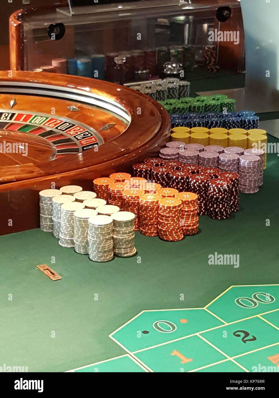 Roulette wheel and chips on a casino table - Stock Image