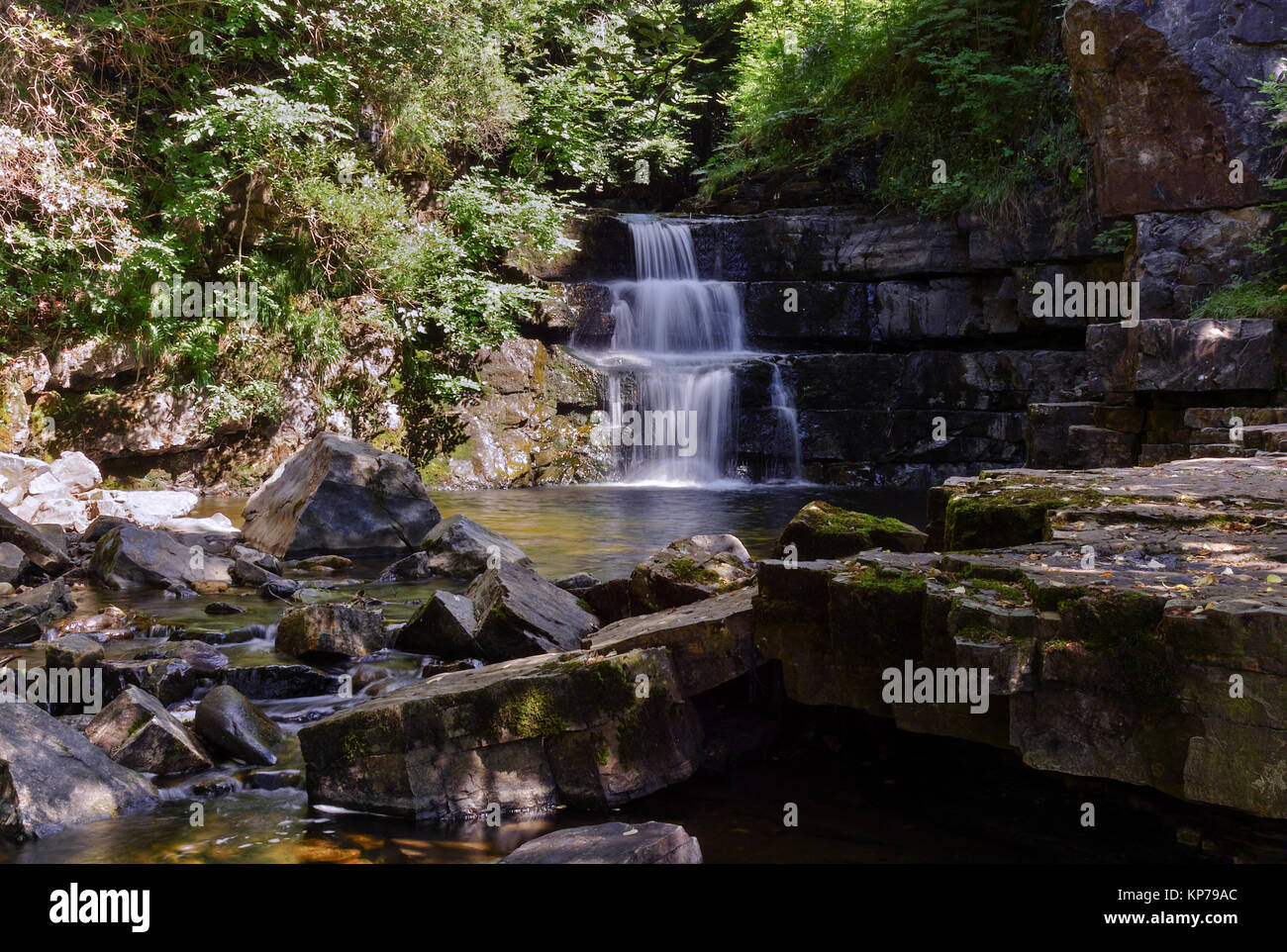 A stepped waterfall at Bowes In Teesdale in County Durham, on a bright sunny day. - Stock Image