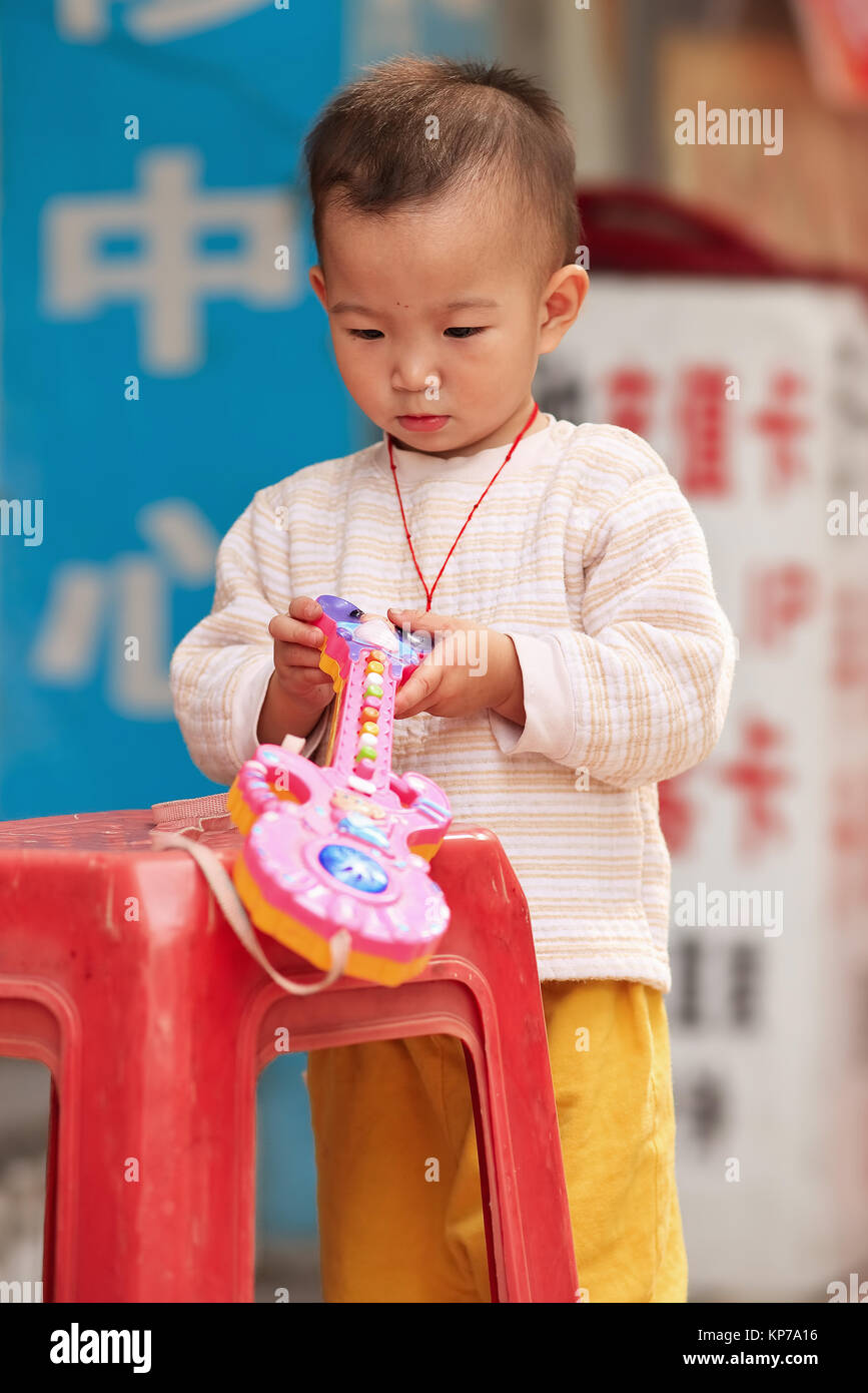 GUANGZHOU-DEC. 13, 2009. Young Chinese boy with a toy. Birth rates in China rose to their highest level as a result - Stock Image