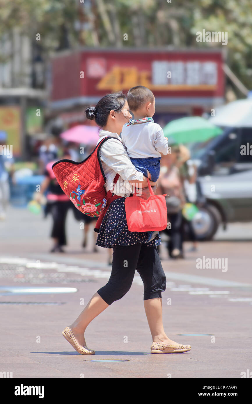 KUNMING-JULI 10, 2014. Chinese woman carry her child. China has ended the one-child policy after 35 years, allow - Stock Image