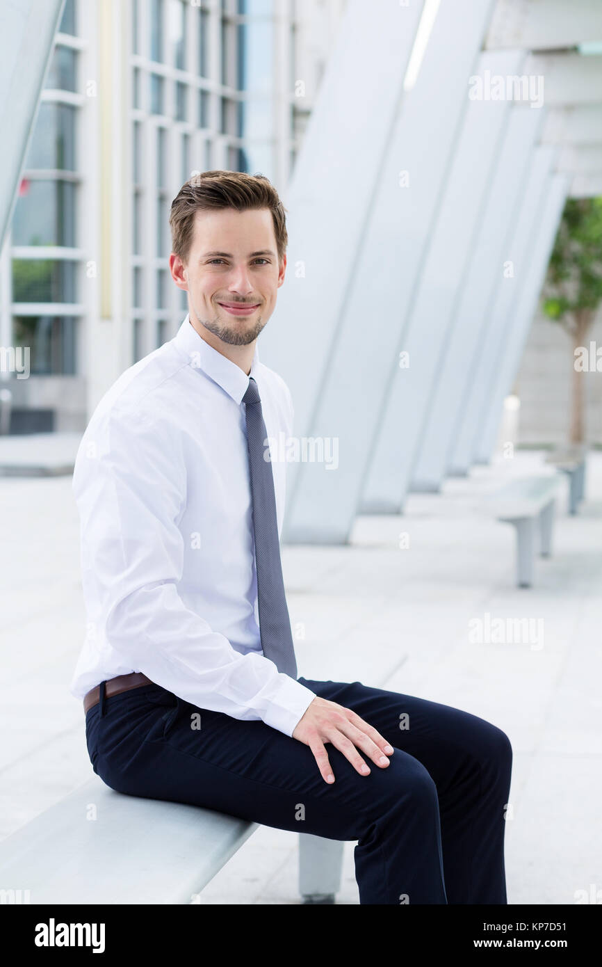 Caucasian businessman sitting on blench at outdoor - Stock Image