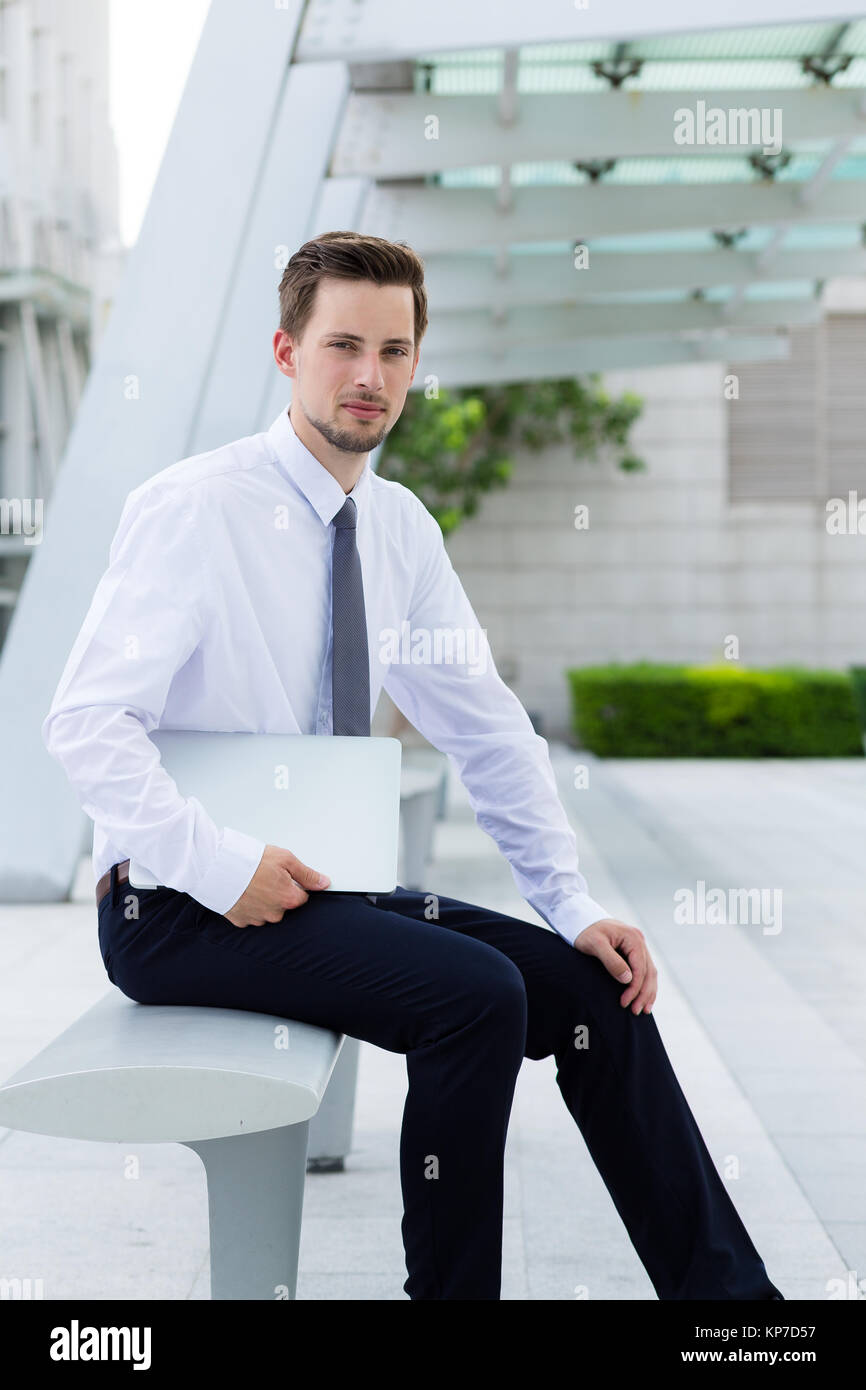Caucasian young businessman hold with laptop computer at hong kong - Stock Image
