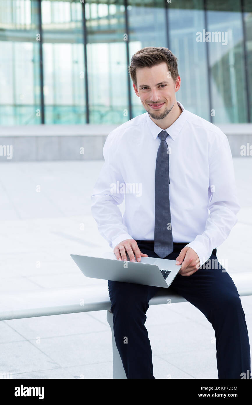 Businessman using the notebook computer at outdoor - Stock Image