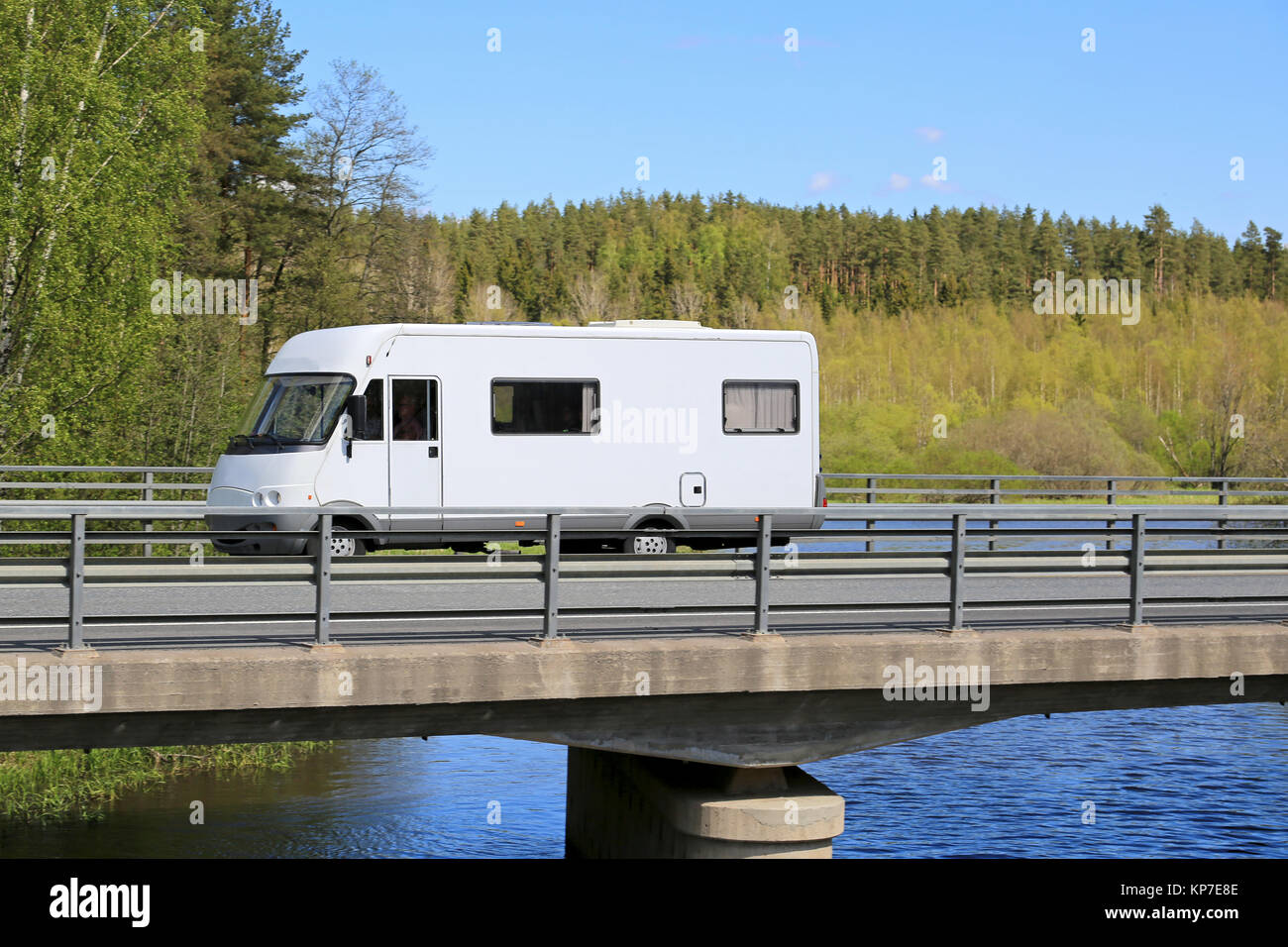 White motorhome traveling along scenic road on a bridge over water at summer. Stock Photo