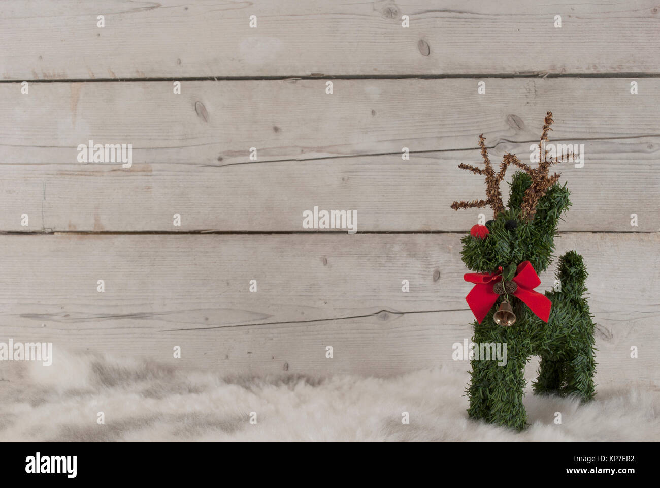 Christmas background, cute reindeer standing on sheepskin, on wooden backdrop - Stock Image