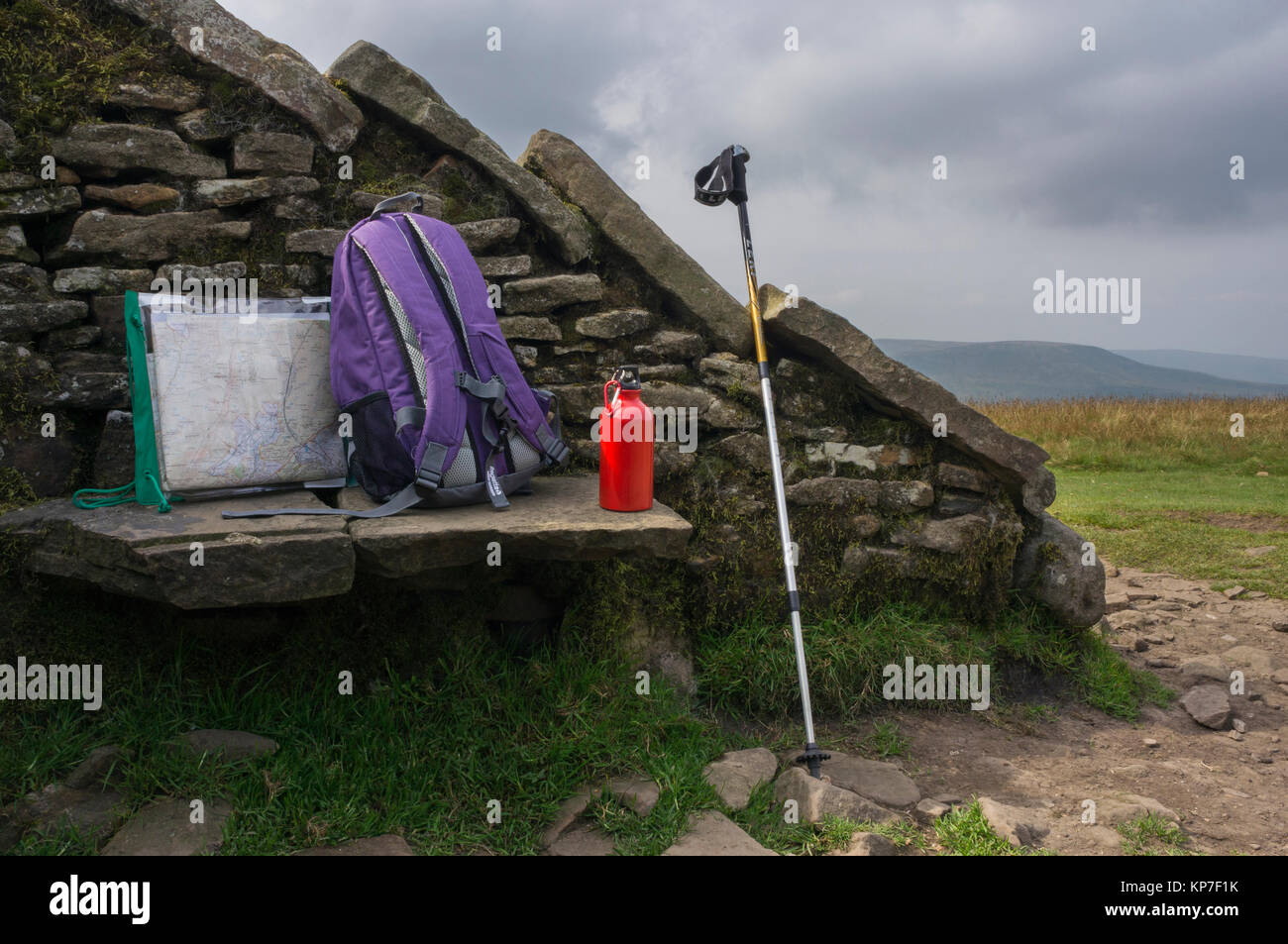 Stone windbreak shelter & seat on summit of Whernside, with map in holder, rucksack,red  water bottle & - Stock Image