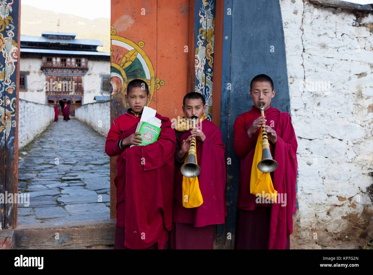 Novice monks with flutes (Rgya-Gling) outside the temple of Wangdichholing Palace built in 1857 as the Kingdom´s - Stock Image