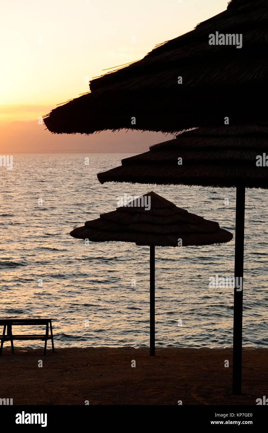 Straw umbrellas on the beach at sunset, Kempinski Hotel, Dead Sea, Jordan, Middle East. - Stock Image