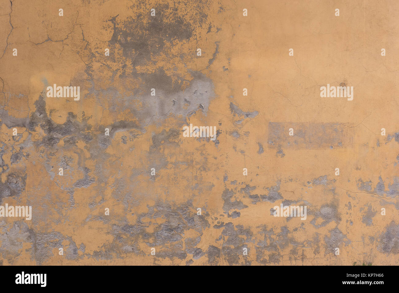 Old cracked yellow wall as background, wallpaper or texture - Stock Image