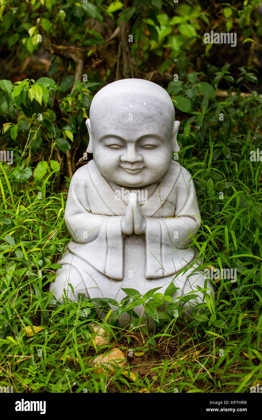Little buddha statue in the garden of a temple in Vietnam - Stock Image