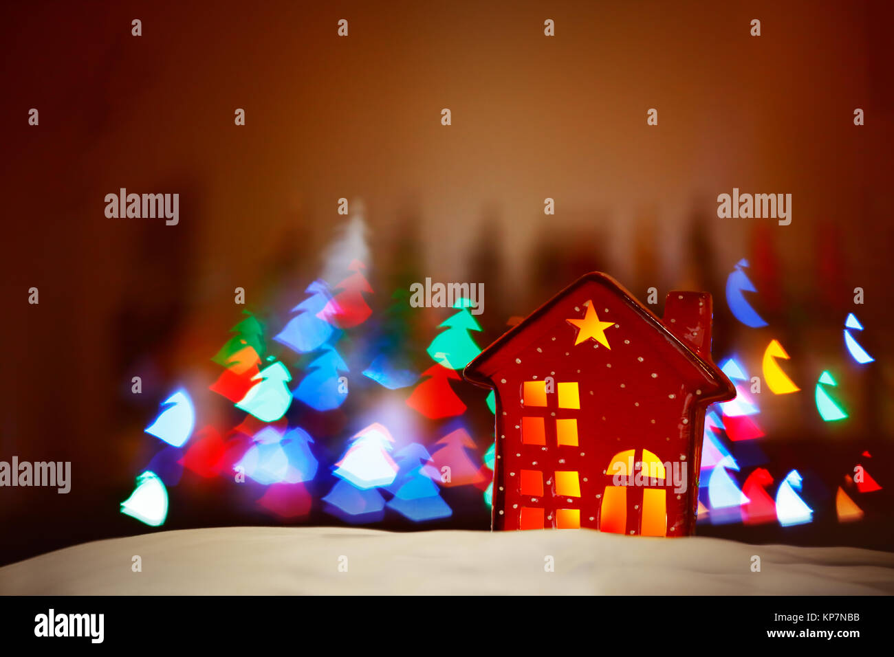 Beautiful Christmas decor, tiny red decorative house over glowing lights background, festive colorful lights in Stock Photo