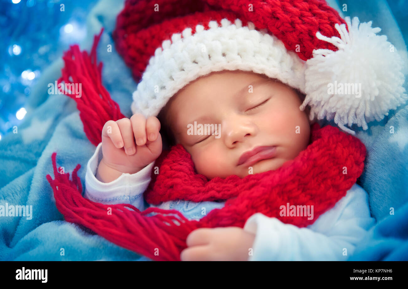 Portrait of a cute newborn baby wearing red knitted Santa hat, sleeping at  home, happy winter holidays, Merry Christmas concept ad79fd232f4
